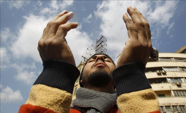 An Egyptian anti-government protester prays at Tahrir Square in downtown Cairo