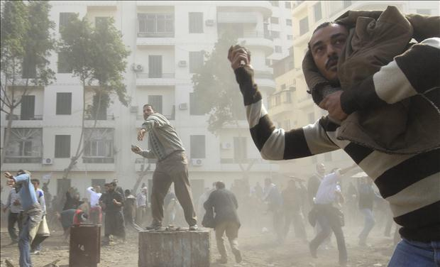 Opposition supporters throw stones at pro-Mubarak demonstrators in Tahrir Square in Cairo
