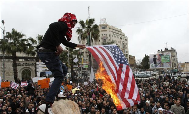 A Palestinian man burns the U.S. flag during a protest in support for Egyptian protesters in Ramallah