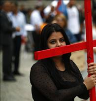 A woman holds a cross during a rally organised by Iraqi Christians