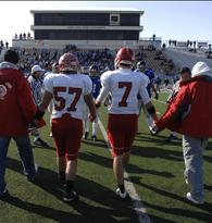 Players hold hands as they take the field for the coin toss with their opponents from Pittsburg-Colgan in Hays