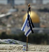 An Israeli flag is placed on the grave of a fallen soldier at the military cemetery on the Mount of Olives in Jerusalem