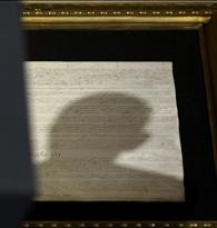 Shadow of head of U.S. President Obama falls upon copy of U.S. Constitution as he makes speech on national security in Washington