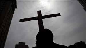 Frank Simmonds, of the Bay Ridge neighborhood of Brooklyn, holds a cross in City Hall Park in New York City