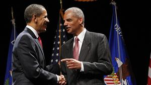 U.S. President Barack Obama speaks with Attorney General Eric Holder during a ceremonial installation at George Washington University in Washington