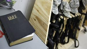 A copy of the holy bible is placed next to rifles during a memorial service for late SFC Johnson in Camp Taji north of Baghdad