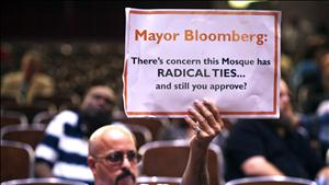 A demonstrator holds a sign during a Landmarks Commission's hearing on the proposed Cordoba Mosque to be built near the site of the former World Trade Center in New York