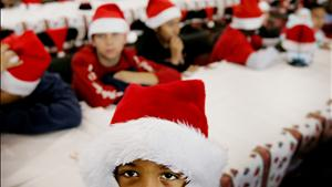 A boy clad in a Santa Claus hat looks on during a Christmas party in Miami.