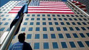 A worker looks up as a seven story flag is hung on the World Financial Center that overlooks ground zero